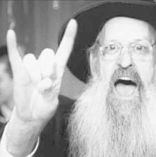 Mittels dem typischen Symbol-Handzeichen Mano Cornuta, zeigt ein orthodoxer Jude seine - bis dato geheim gebliebene - Verbindung mit der globalen Verschwörung der Hard and Heavy-Metall (Kiss) Anhänger.