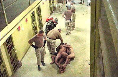 Die Soldaten bringen nackte, gefesselte und mit Kapuzen versehene Gefangene in Positionen, die einen sexuellen Verkehr vortäuschen sollen.