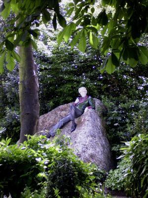 Eine Figur auf einem Stein in einem Park in Dublin, die den Autoren Oscar Wilde darstellt.