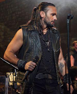 Muskulüser Mann mit dunker Lederweste, Tattoos am Arm und langen Haaren