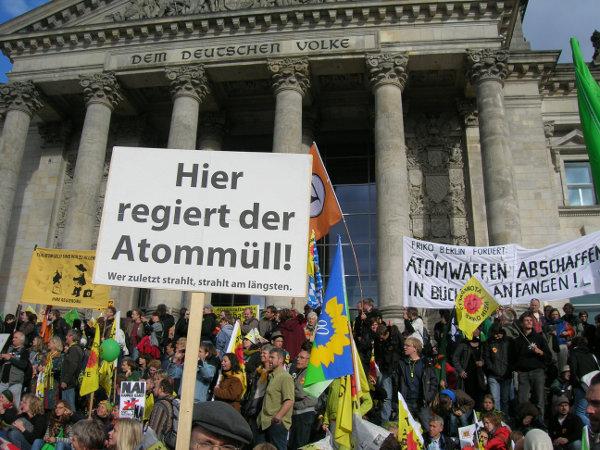 """besetzte Reichstagstreppen während Anti-Atom-Demo vom 18.9.2010 in Berlin. U.a. steht auf einem Schild """"Hier regiert der Atommüll! - Wer zuletzt strahlt, strahlt am längsten."""""""