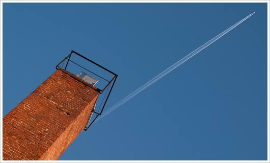 Flugzeug mit Kondensstreifen an blauem Himmel