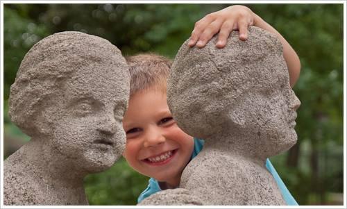 Ein Junde zwischen zwei Steinfiguren