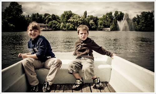 Junge und Mädchen im Heck eines Ruderbootes