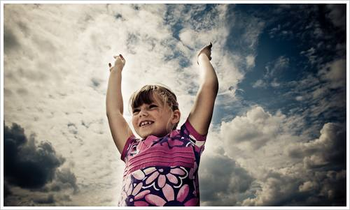 Ein Mädchen vor einem bewölkten Himmel
