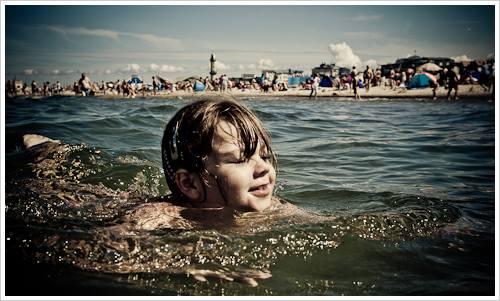 Ein Mädchen schwimmt im Meer, im Hintergrund der Strand mit Menschen
