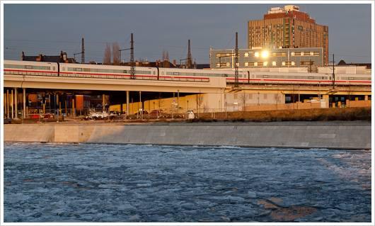ICE fährt über Viadukt, unten Eis im Fluss