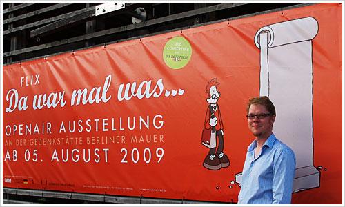 Flix vor dem Plakat der Ausstellung