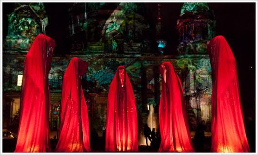 Rote Figuren vor beleuchteter Kirche