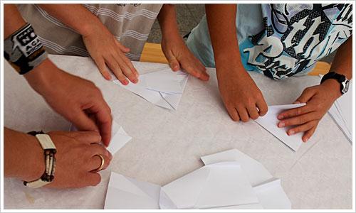 Kinder beim Falten von Papierfliegern