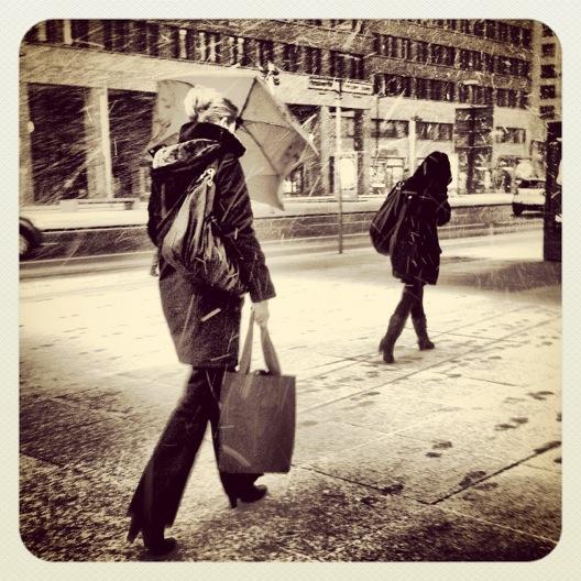 Zwei Personen laufen im Schnee die Strasse entlang