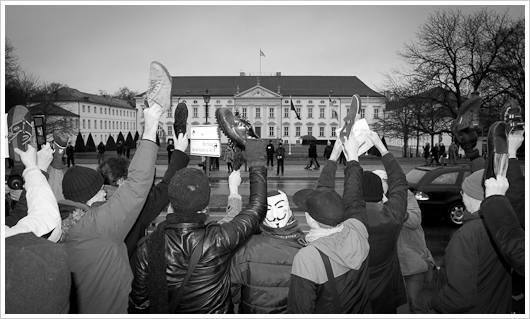 Demonstranten halten Schuhe in die Luft