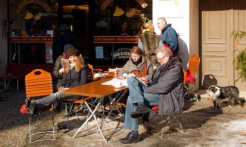 Menschen vor einem Cafe in der Sonne