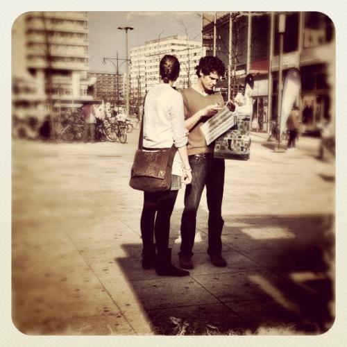 Mann und Frau auf einem Platz studieren einen Stadtplan