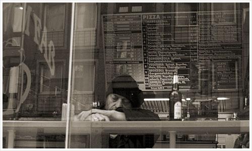Mann durch Fenster einer Kneipe