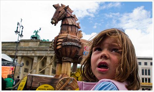 Kind mit trojanischem Pferd vor dem Brandenburger Tor