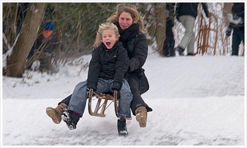 Ein Schlitten mit zwei Personen springt über eine Schneekante