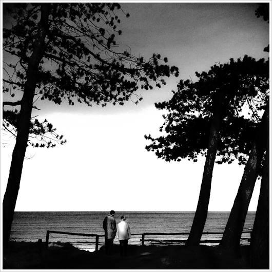 Zwie Personen blicken auf das Meer